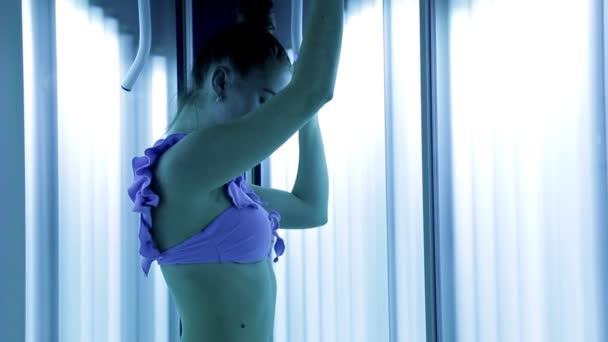 A beautiful girl with a healthy body standing in the Solarium of the Spa has a beautiful figure. Tan, skin