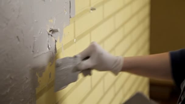 Girl in white gloves puts a wall in front of the repair. Spatula, plaster. Smooth walls