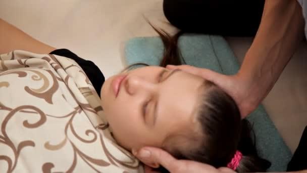 Nahaufnahme eines kleinen Mädchens bei einer osteopathischen Therapiesitzung. Der Therapeut manipuliert den Kopf des Kindes. Massage im Spa