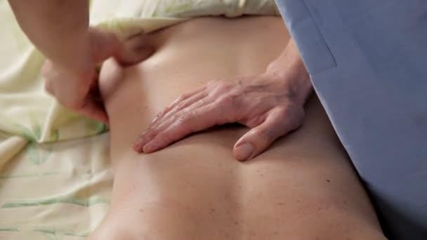 Physiotherapeut in der Klinik gibt einer Frau eine Massage zurück