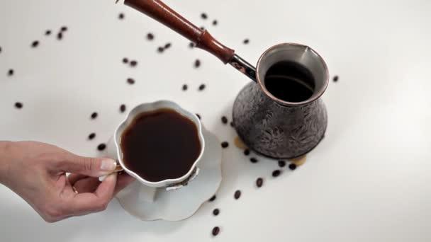 A nő ömlött forró aromás kávét egy csésze egy fehér asztal, amelyen a kávébab szétszóródtak. Reggelente finom kávé, ébredés