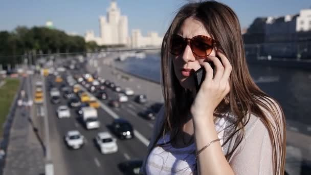 Beautiful attractive young woman standing on the bridge and uses a smartphone. Below is a stream of cars