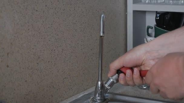 Reparatur von Wasserleitungen nach Wasserlecks. Hände eines Mannes, der in seiner Wohnung einen Wasserhahn in der Küche repariert