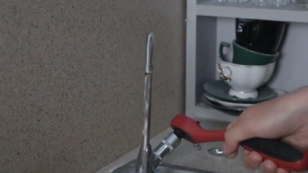 Instalatérská oprava z úniku vody. Ruce muže, který opravuje kohoutek v kuchyni ve svém bytě