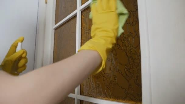 Ruce ženy v domácnosti v žlutých ochranných rukavicích čistí špinavé okno ve dveřích. Koncept domácích prací a služeb