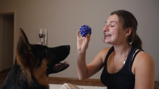 Portrait of beautiful young woman with her dog playing with ball at home