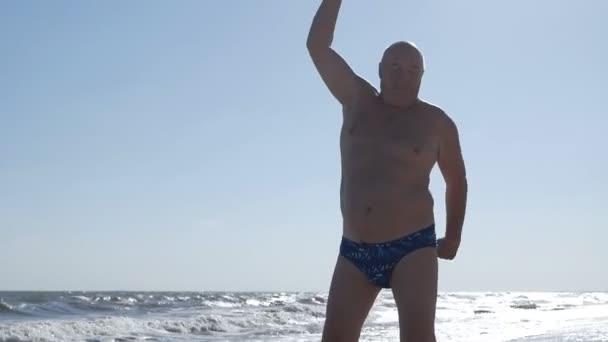 Blick auf einen älteren Mann, der am Strand Sport treibt. Schöner Himmel und Meer im Hintergrund. Reifer alter mann, gesund fit opa working out auf die strand