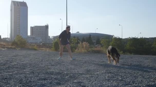 Mladá žena běží a hraje si se svým německým ovčákem. Žena na procházce se svým psem.