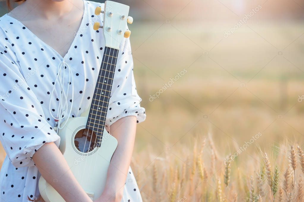 Beautiful asian woman playing ukulele and relaxing at barley field in summer on sunset time