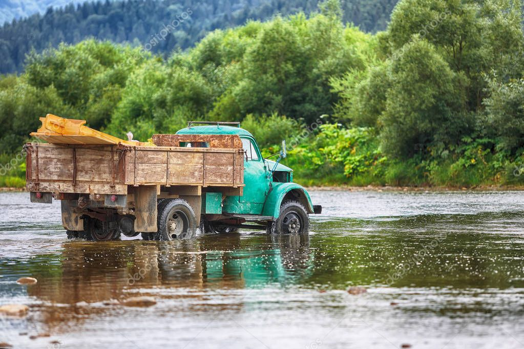 old truck transports cargo wade across the river. Old dirty truck