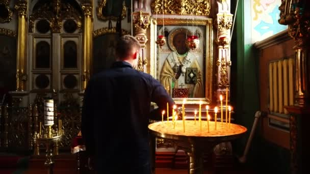 A man prays and worships the icon of St. Nicholas. A man in a Christian Church.