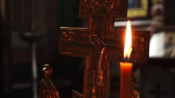 A láng egy gyertyát, a háttérben a keresztre feszítés, Jézus Krisztus. Videóinak közelről.