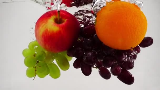 Apple, orange and grapes falling into water with bubbles in slow motion. Fruit on white background.