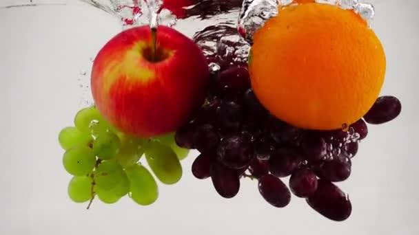 Jablečný, pomerančový a hrozny révy vinné do vody s bublinkami v pomalém pohybu. Ovoce na bílém pozadí.