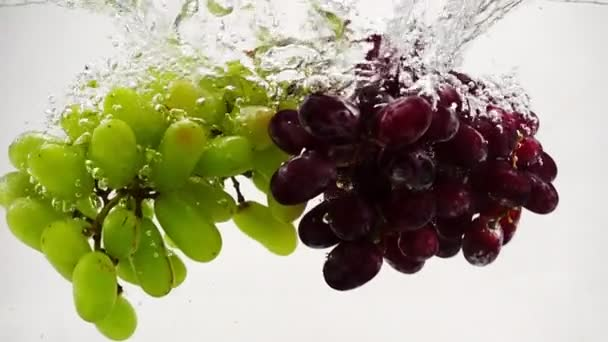 Červené a zelené hrozny pádu do vody s bublinkami v pomalém pohybu. Ovoce na bílém pozadí