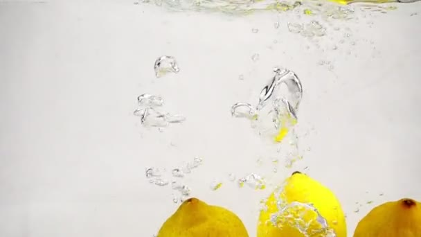 Video of lemons in slow motion on white background. Ripe yellow fruits are immersed in water with bubbles.