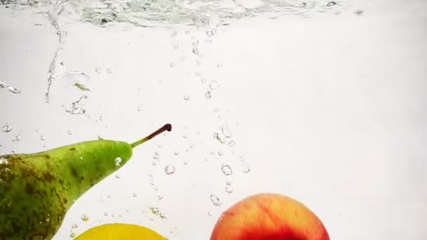 Slow motion fruit with bubbles. Whole lemon, apple and pear fall into a transparent container with water.