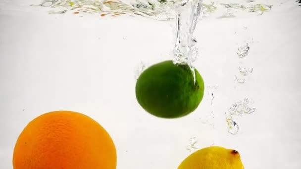 Zitrone, Orange und Limette fallen ins Wasser. Zeitlupe Frucht mit Blasen auf isoliertem Hintergrund.