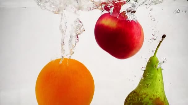 Slow motion video of pear, apple and orange falling into water with bubbles. Fruits on isolated white background.