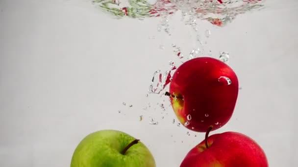 Zpomalené video z červené a zelené jablko padá do vody s bublinkami. Ovoce na izolované bílém pozadí.