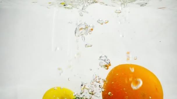 Zeitlupenvideo von Zitrone, Limette und Orange, die mit Blasen ins Wasser fallen.