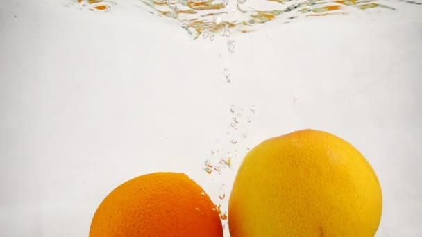 A whole grapefruit and orange falls into the water with bubbles. Video of citrus fruit in slow motion.