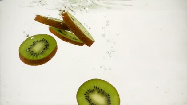 Fruit slices of kiwi fall into the water on a white background close-up