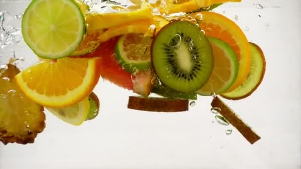 Multifruit cocktail, pieces of fruit falling into the water with splashes and bubbles, slow motion close-up
