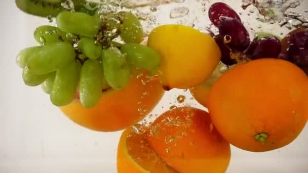 Juicy halves of fruit fall into the water, multifruit set, slow motion close-up