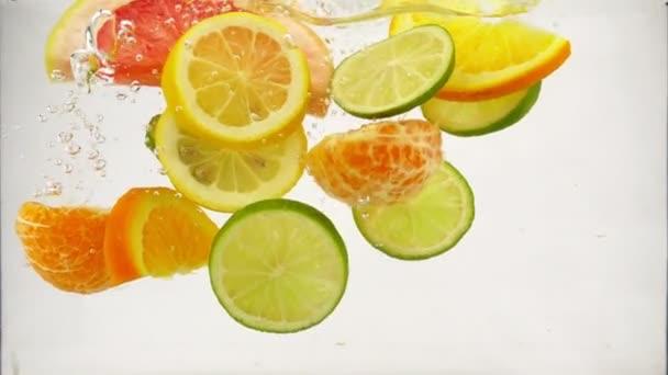 Kousky z citrusových plodů mandarinky, limetka, citron, pomeranč, grapefruit spadají do vody s sprej a bubliny, zpomalené detail