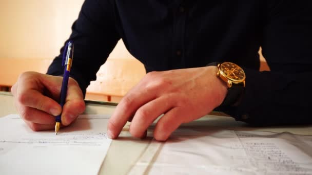 A businessman with a gold watch on his hand signs documents. The video was shot close-up.