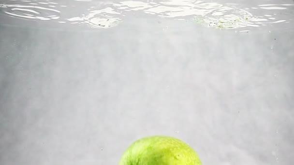 Zelené jablko padá do vody pomalým tempem. Ovoce izolovaných na bílém pozadí.