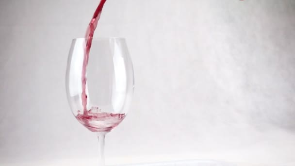 Pouring wine into a glass with drops in slow motion