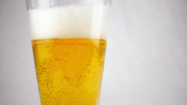 Pivní sklo detail. Sklenice pivní pěny a bublin v pomalém pohybu