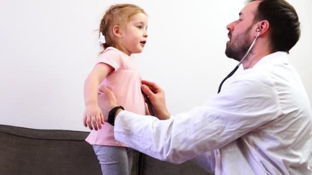 Einen Arzt hören Lunge Arbeit ein kleines Mädchen mit seinem Stethoskop.