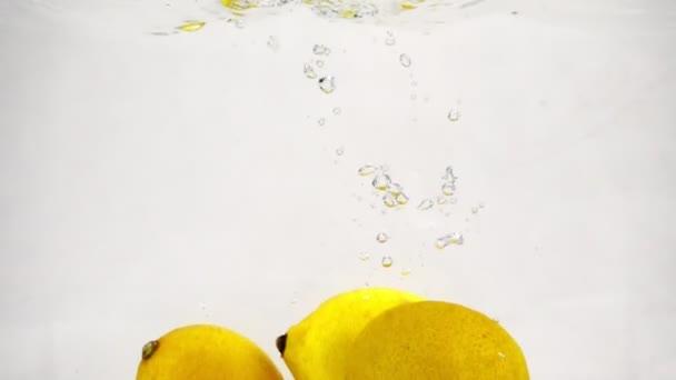 Video z citronů v pomalém pohybu. Zralé plody se ponoří do vody s bublinkami