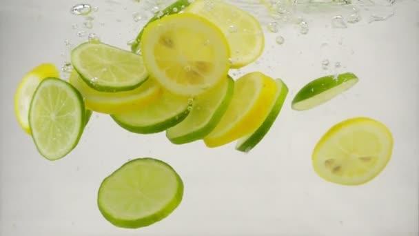 Zitruslimousinen- und Zitronenscheiben fallen mit Spritzern und Blasen ins Wasser, Zeitlupe Nahaufnahme
