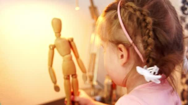 Ein kleines Mädchen ein Spiel mit einem aufklappbaren Holzpuppe.