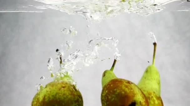Zelené hrušky spadá do vody se spoustou malých bublinek. Video z ovoce na izolované bílém pozadí.
