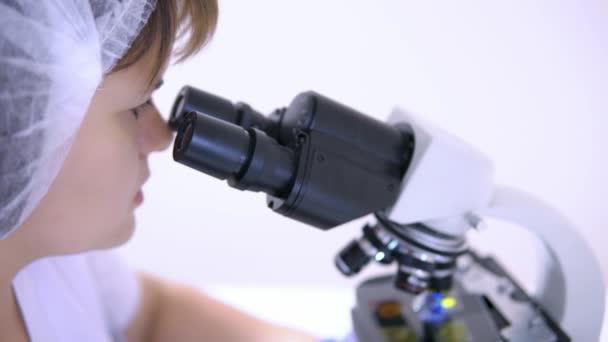 Szembe a fiatal nő labor technikus nézi a Mikroszkóp szemlencse