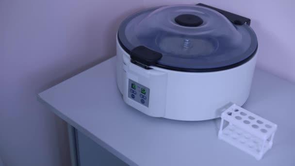 Laboratory technician in a laboratory presses a button start on centrifuge