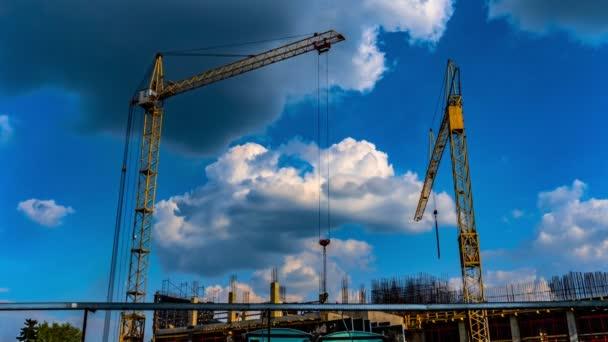 Tři žluté stavební jeřáby pracují na místě stavby v době výstavby propadů