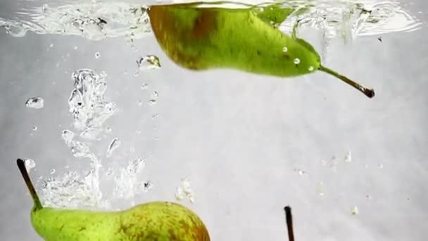 Hruška se ponoří do zásobníku vody s bublinkami v pomalém pohybu. Plody na izolovaném bílém pozadí.