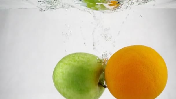Orange and green apple whirling in water with bubbles at a slow motion.