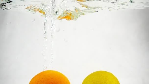 Vápno a pomeranč klesají do vody na izolovaném pozadí. Video Citrus v pomalém pohybu.