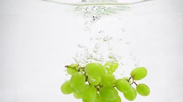 Zelené hrozny se nacházejí na dně průhledné nádoby s vodou. Pomalý pohyb videa.