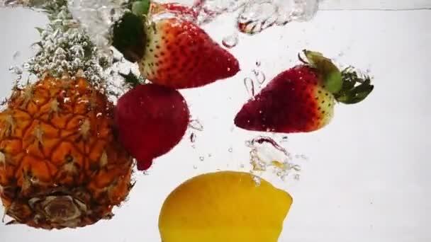 Ananas, citron a jahoda vířící ve vodě s bublinkami ve zpomaleném pohybu.
