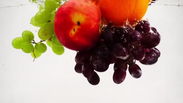 The orange, apple and grapes falling in water with bubbles. Video in slow motion. Fruits on isolated a white background.