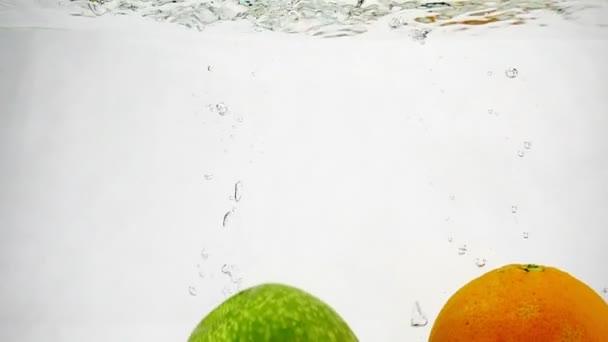 Ananas a jablko padají do vody se spoustou bublin. Video ovoce na izolovaném bílém pozadí.