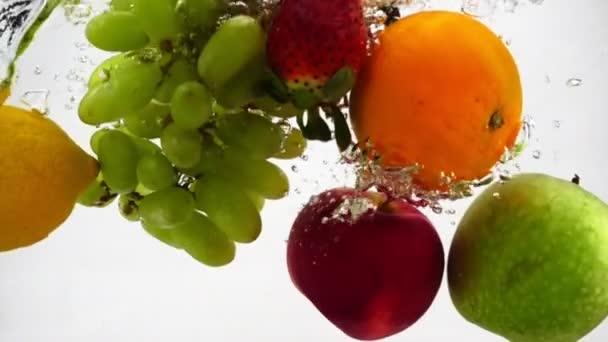 Jablko, kiwi, pomeranč, hruška, citron, hrozny a jahody padají do vody s bublinkami. Videografie ve zpomaleném filmu